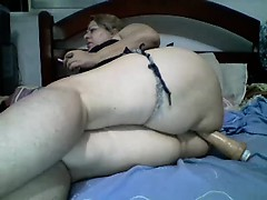 Chubby blonde lady lies on the bed and fucks her holes with