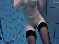 anetta swims in a pool in her nylon stockings and a corset
